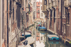 VENICE, ITALY - MARCH 17, 2016. Urban canal and boats on it, on a gloomy day in Venice, Italy. Vintage filter. Stock Image