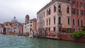 VENICE, Italy - May 2019: camera glides like a boat along a grand canal. Many typical houses and green spaces on them