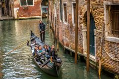 Gondola with happy people sail on an old canal in Venice. Venice, Italy - May 20, 2017: Gondola with happy people sail on an old canal in Venice. Romantic water royalty free stock photos