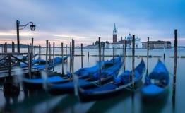 Venice, Italy - 20 May 2105: Gondolas moored on the lagoon, with Royalty Free Stock Photo