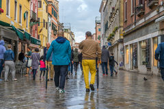 VENICE, ITALY - May 23, 2016: Male couple in colorful cloths from back walking through Venice streets after storm with umbrellas b Stock Photos