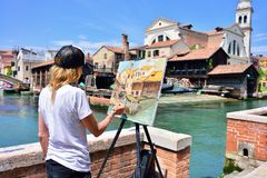 VENICE, ITALY - MAY, 2017: A woman paints with oil on canvas the. View of the gondolas workshop in Venice stock photo