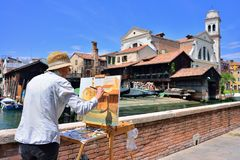 VENICE, ITALY - MAY, 2017: A woman paints with oil on canvas the. View of the gondolas workshop in Venice stock photos