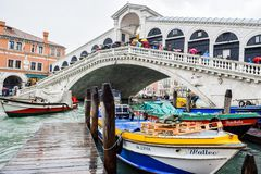 Tourists on a rainy day at Rialto Bridge on the Grand Canal in Venice, Italy royalty free stock image