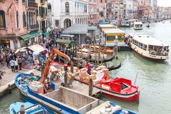 VENICE, ITALY - NOVEMBER 23, 2015: two men are unloading sacks from the boat in Venice, Italy royalty free stock images
