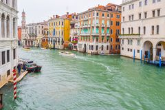 Water taxis/ taxi cabs and other boats sailing on water between colorful gothic Venetian buildings on a rainy day in Venice stock images