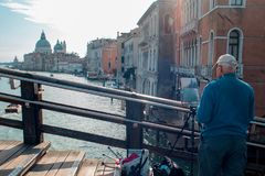 VENICE, ITALY - OCTOBER 8 , 2017: The artist on the bridge of Academy, makes a watercolor painting. VENICE, ITALY - OCTOBER 8 , 2017: The artist on the bridge of stock image