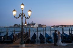 VENICE, ITALY - OCTOBER 7 , 2017: bride and groom on Piazza San Marco, gondolas on the background. VENICE, ITALY - OCTOBER 7, 2017: bride and groom hugging on Royalty Free Stock Image