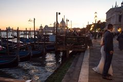 VENICE, ITALY - OCTOBER 7 , 2017: bride and groom on Piazza San Marco, gondolas on the background. VENICE, ITALY - OCTOBER 7, 2017: bride and groom hugging on Royalty Free Stock Images