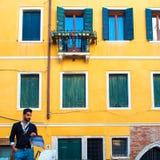 VENICE, ITALY - OCTOBER 7 , 2017: Elegant man on background of yellow wall Italian buildings. VENICE, ITALY - OCTOBER 7 , 2017: Elegant man on a background of Stock Images