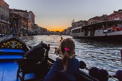 VENICE, ITALY - OCTOBER 27, 2016: A Gondola on the Grand Canal glides toward the Rialto Bridge in Venice Italy royalty free stock photo