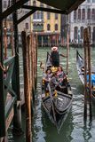 Venice, Italy - October 13, 2017: The gondola with tourists is moored at the pier. Royalty Free Stock Photos