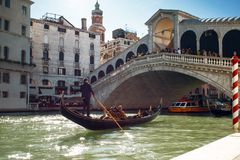 VENICE, ITALY - OCTOBER 7 , 2017: Gondolier floats on the Grand Canal, the Rialto bridge in the background. VENICE, ITALY - OCTOBER 7 , 2017: Gondolier floats on Royalty Free Stock Photography