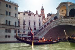 VENICE, ITALY - OCTOBER 7 , 2017: Gondolier floats on the Grand Canal, the Rialto bridge in the background. VENICE, ITALY - OCTOBER 7 , 2017: Gondolier floats on Stock Photo