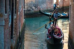 VENICE, ITALY - OCTOBER 7 , 2017: Gondolier floats on the narrow channel in Venice, Italy. VENICE, ITALY - OCTOBER 7 , 2017: Gondolier floats on the narrow Royalty Free Stock Photography