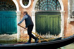 VENICE, ITALY - OCTOBER 8 , 2017: Gondolier floats on the narrow channel in Venice, Italy. VENICE, ITALY - OCTOBER 8 , 2017: Gondolier floats on the narrow Royalty Free Stock Image