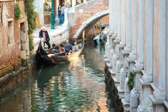 VENICE, ITALY - OCTOBER 7 , 2017: Gondolier floats on the narrow channel in Venice, Italy. VENICE, ITALY - OCTOBER 7 , 2017: Gondolier floats on the narrow Stock Photo