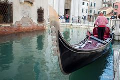VENICE, ITALY - OCTOBER 8 , 2017: Gondolier floats on the narrow channel in Venice, Italy. VENICE, ITALY - OCTOBER 8 , 2017: Gondolier floats on the narrow Royalty Free Stock Photography