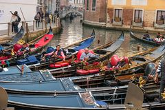 Venice, Italy - October 13, 2017: Gondoliers rest in their gondolas. The gondoliers joke and laugh. Royalty Free Stock Photography