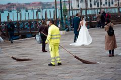 VENICE, ITALY - OCTOBER 8 , 2017: A lot of people on San Marco square, janitor in uniform. VENICE, ITALY - OCTOBER 8, 2017: A lot of people on San Marco square Royalty Free Stock Photo