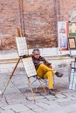 VENICE, ITALY - OCTOBER 27, 2016: A painter Painting canvas on street in Venice, Italy. VENICE, ITALY - OCTOBER 27, 2016: A painter Painting canvas on street and royalty free stock photos