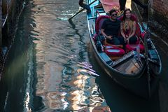 VENICE, ITALY - OCTOBER 7 , 2017: Tourists in a gondola enjoying the ride in Venice, Italy. VENICE, ITALY - OCTOBER 7 , 2017: Tourists in a gondola enjoying the Stock Photography