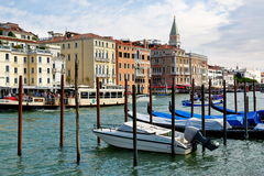 Venice, Italy. Parked motor boat and gondolas near wooden posts Royalty Free Stock Photography