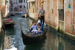 Gondola with Chinese tourists on the city channel. Venice, Italy Royalty Free Stock Photo