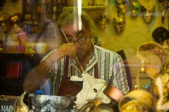 Venice. Italy. September 8, 2018.The master in his workshop at the store makes masquerade masks. In Venice stock photo