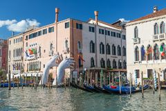 VENICE, ITALY - SEPTEMBER, 2017: Monumental big hands rise from the water in Venice to highlight climate change with blue sky. VENICE, ITALY - SEPTEMBER, 2017 Stock Image