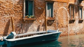 VENICE, ITALY, SEPTEMBER 7, 2017: Motor boat stands on a Venetian canal under a beautiful vintage brick wall and windows. VENICE, ITALY, SEPTEMBER 7, 2017: A stock video