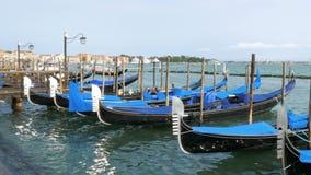 Docked empty gondolas on wooden mooring piles. Venice, Italy stock footage
