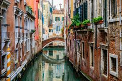 Weathered building facade on a picturesque canal in Venice Italy. Venice, Italy - September 23, 2017: Typical view of a weathered building facade and bridge on a royalty free stock images