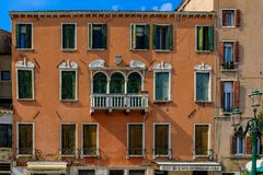 Weathered building facade on a picturesque canal in Venice Italy. Venice, Italy - September 23, 2017: Typical view of a weathered building facade in a Venetian stock image