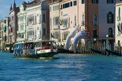 Vaporetto swims by Lorenzo Quinn`s sculpture Support on the Grand Canal, Venice Royalty Free Stock Images