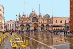 St Mark`s Square full of tourists during a flood with beautiful water reflections of St. Marks churchl. VENICE,ITALY 10.11.2016. St Mark`s Square full of stock photography