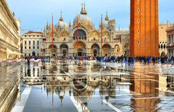 VENICE,ITALY 10.11.2016 St Mark`s Square full of tourists during a flood with beautiful water reflections of St. Marks Cathedral. VENICE,ITALY St Mark`s Square stock image