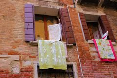 Venice, Italy. Tourist, tourism, old, architecture, city, house, window, brick, yellow, green, laundry, shutter, lace Stock Photo