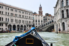 VENICE-JUNE 15 :在威尼斯式大运河的长平底船有2012年6月15日的Rialto桥梁的在威尼斯,意大利。 图库摄影