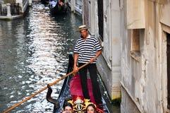 VENICE-JUNE 15 :平底船的船夫在威尼斯跑有小组的长平底船威尼斯式运河的游人2012年6月15日,意大利。 图库摄影