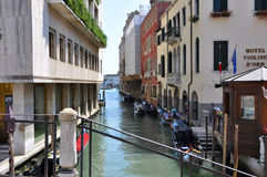 VENICE-JUNE 15 :有长平底船的狭窄的威尼斯式运河2012年6月15日在威尼斯,意大利。 库存图片