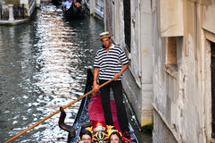 VENICE-JUNE 15: Gondolier runs the gondola with group of tourists on the Venetian canal on June 15, 2012 in Venice, Italy. Stock Photography