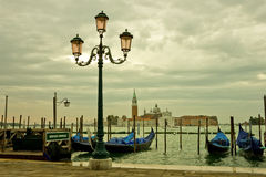 Venice Lagoon in a Moody Sunrise. Venice lagoon with beautiful lamp post, gondolas and San Giorgio Maggiore in a moody early morning Royalty Free Stock Photos