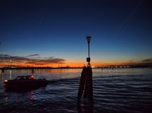 Venice lagoon at night with a navigation buoy and boat in silhouette with a sunset glow and city lights reflected in the dark. The venice lagoon at night with a royalty free stock photography