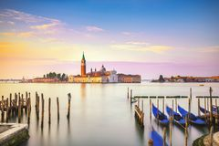 Venice lagoon, San Giorgio church, gondolas and poles. Italy Stock Photography