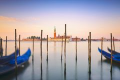 Venice lagoon, San Giorgio church, gondolas and poles. Italy stock images