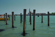 Venice, the lagoon and San Giorgio island. Boat poles in the venetian lagoon. View od the San Giorgio island, Venezia, Italy royalty free stock photos