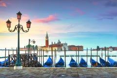 Venice lagoon, San Giorgio church, gondolas and poles. Italy stock photo