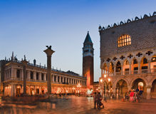 Venice Marco Crowd Doges Set. Doges palace, Campanile bell tower and Venice republic coat of arms lion on tall column at San Marco square at sunset Royalty Free Stock Photo