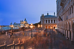 Venice Marco Crowd Pier Maria Set. San Marco square of Venice at sunset along Doges palace towards Gondola service piers and Di Santa Maria catherdal. blurred Royalty Free Stock Images
